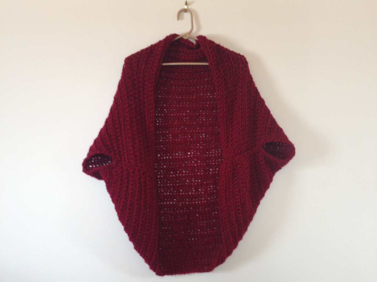 Finished boho crochet shrug cardigan hanging on the wall