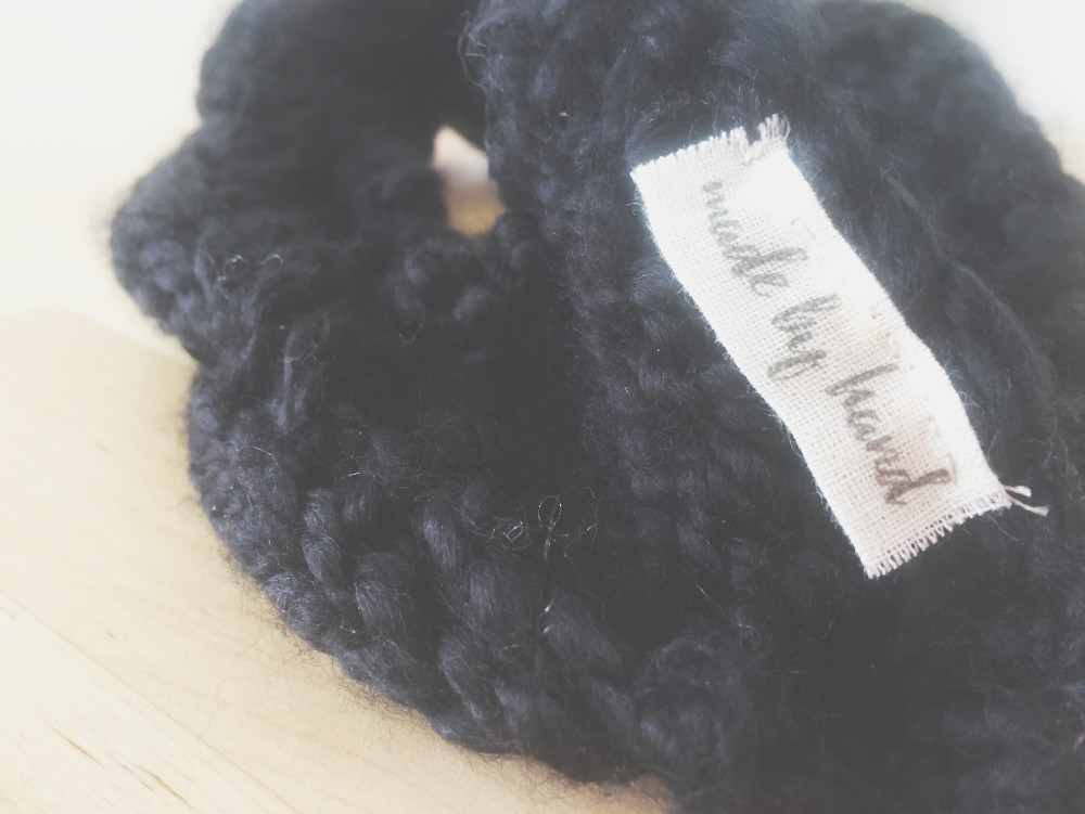 folded label attached to a cable knit headband