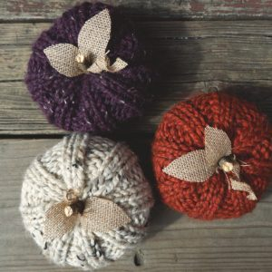 3 knit pumpkins with burlap leaves and a twig stem